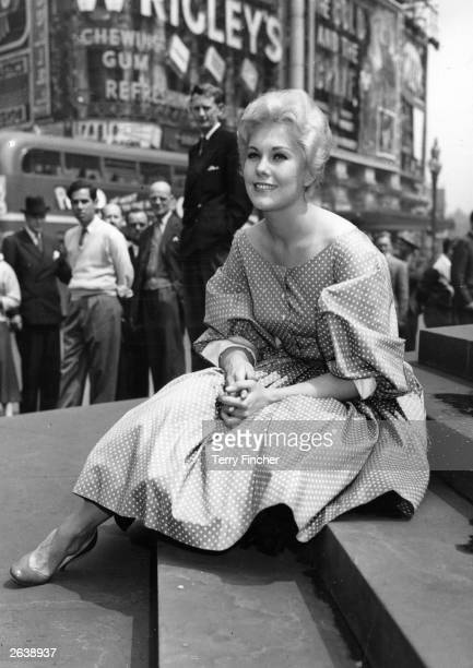 US actress Kim Novak takes a break at Piccadilly Circus while on a sightseeing tour of London which was filmed for television Original Publication...