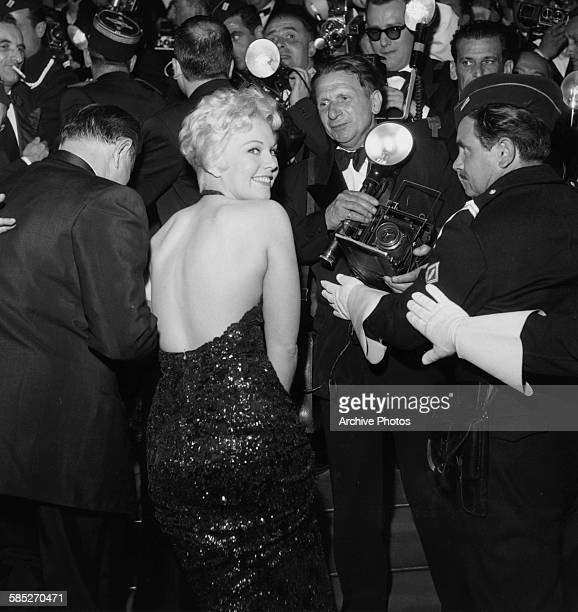 Actress Kim Novak wearing a sequin backless dress as she attends the Cannes Film Festival April 24th 1956