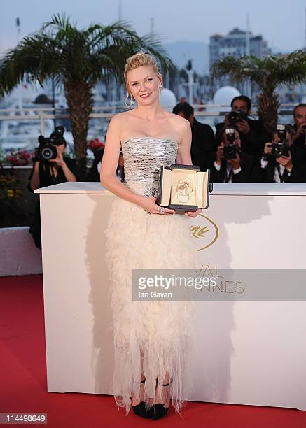 Actress Kirsten Dunst poses after winning Best Actress for the film Melancholia at the Palme d'Or Winners Photocall at the Palais des Festivals...