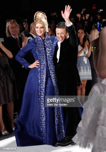 Actress Kirstie Alley and fashion designer Zang Toi walk the runway in the Zang Toi Spring 2012 fashion show during MercedesBenz Fashion Week at The...