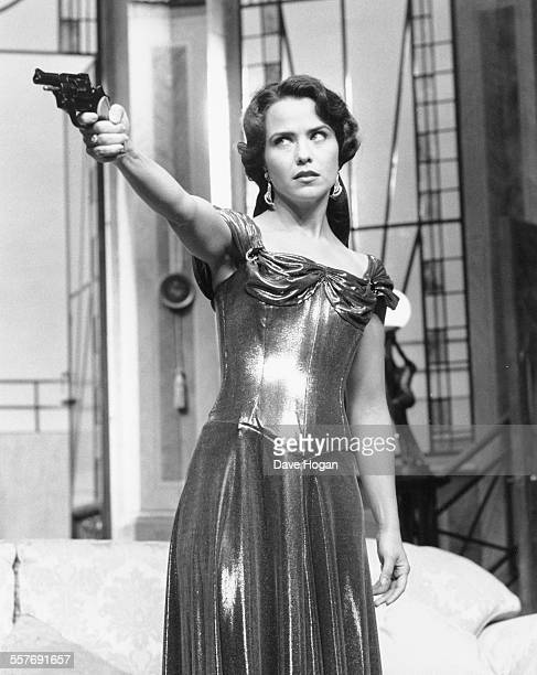 Actress Koo Stark wearing a ball gown and pointing a gun during rehearsals for the Agatha Christie play 'And Then There Were None' at the Duke of...