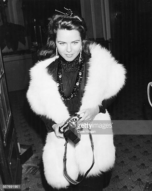 Actress Koo Stark wearing a fur stole and holding a camera arriving at Camden Palace in London February 17th 1984