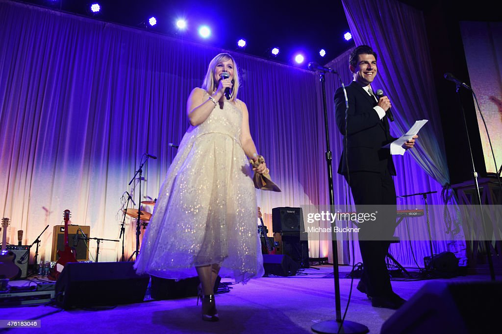 Actress Kristen Bell (L) and host Max Greenfield speak onstage at the 14th annual Chrysalis Butterfly Ball sponsored by Audi, Kayne Anderson, Lauren B. Beauty and Z Gallerie on June 6, 2015 in Los Angeles, California.