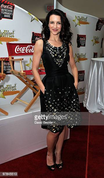 Actress Kristen Davis poses by a director's chair for a charity auction for CocaCola before the ShoWest final night banquet and awards ceremony at...