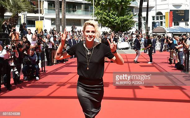 US actress Kristen Stewart flashes victory signs on May 15 2016 as she arrives for the screening of the film 'American Honey' at the 69th Cannes Film...