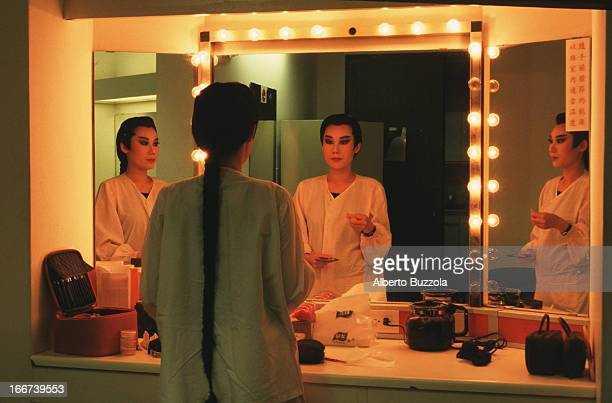Actress Kuo Chunmei looking in the mirror before going onstage at the HoLo Taiwanese Opera House