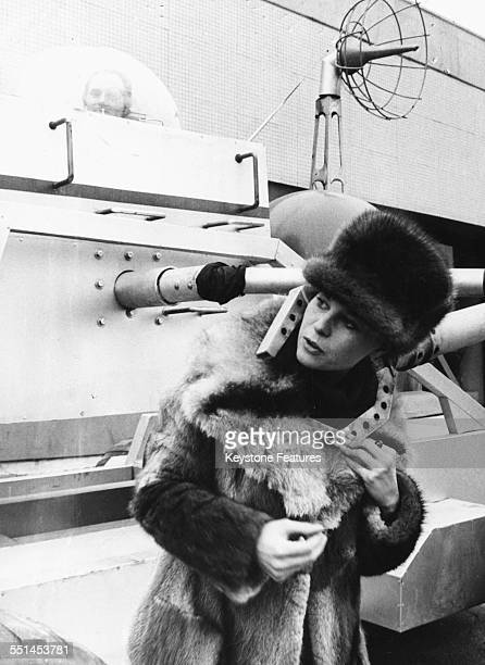 Actress Lana Wood wearing a fur coat and hat as she jokes around with a 'robot' promoting the James Bond film 'Diamonds are Forever' in Dusseldorf...