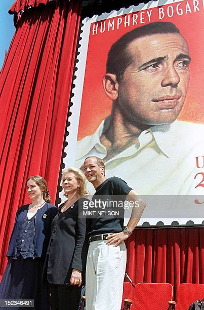 Actress Lauren Bacall and her two children Stephen and Leslie by former husband Humphrey Bogart pose in front of a stamp commemorating his life 31...