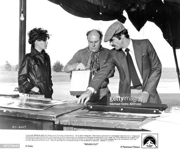 """Actress Lesley-Anne Down with actors Timothy West and Burt Reynolds on set of the Paramount Pictures movie """"Rough Cut"""" in 1980."""