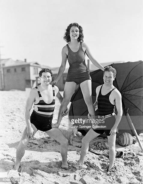 Actress Lillian Roth stands on the legs of fellow actors Harry Green and Regis Toomey