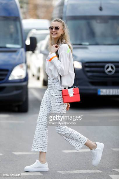 Actress Lilly Krug wearing a red and white bag with black shoulder strap and gold details by Emporio Armani, a white blouse with neon colored details...