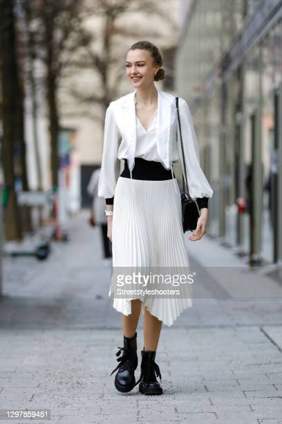 Actress Lilly Krug wearing black boots by Kennel & Schmenger, a black bag with silver studs by Yves Saint Laurent and a midi length black and cream...