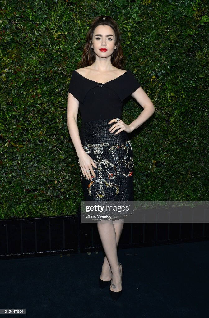 Actress Lily Collins, wearing CHANEL, attends the Charles Finch and CHANEL Pre-Oscar Awards Dinner at Madeo Restaurant on February 25, 2017 in Beverly Hills, California.