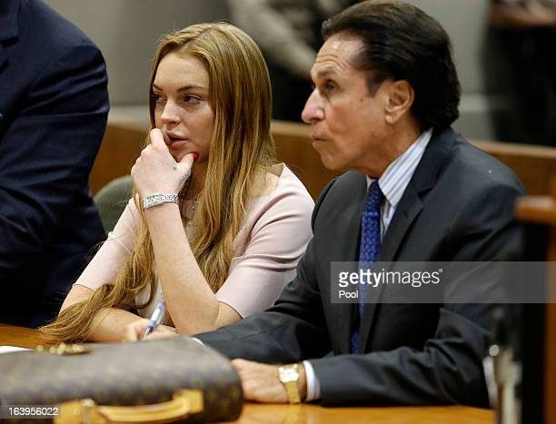 Actress Lindsay Lohan and attorney Mark Heller listen at a hearing in Los Angeles Superior Court on March 18 2013 in Los Angeles California The...