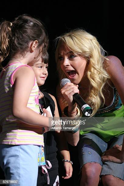 Actress Lindsay Lohan appears on stage with two unidentified children for the Y100.7FM Summer Splash Concert at The Office Depot Center on May 24,...