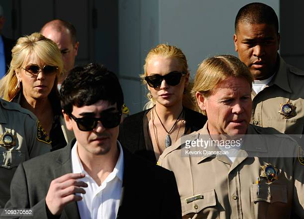 Actress Lindsay Lohan her mother Dina Lohan and brother Michael Lohan Jr. Are escorted by Los Angeles County Sherriff deputies as they leave the...