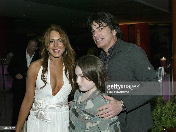 Actress Lindsay Lohan poses for a photo with actor Peter Gallagher and Peter's daughter Catherine during the Mean Girl After Party on April 23 2004...