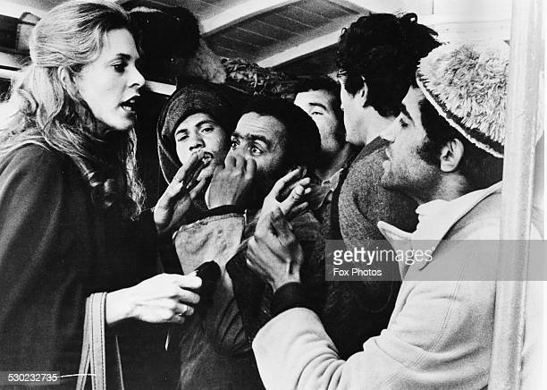 Actress Lindsay Wagner arguing with a group of Moroccan hashish sellers in a scene from the film 'Two People' February 1974
