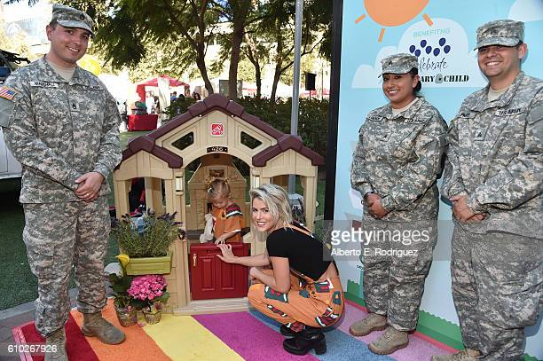 Actress Linsey Godfrey poses with members of the US Army National Guard attend the Step2 Favoredby Present The 5th Annual Red Carpet Safety Awareness...