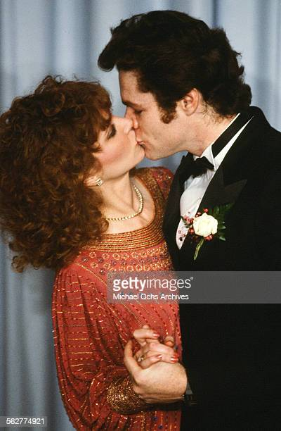 Actress Lisa Eilbacher and actor David Keith kiss backstage during the 55th Academy Awards at Dorothy Chandler Pavilion Los Angeles California