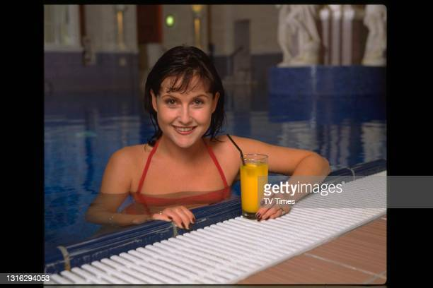 Actress Liz Carling in a swimming pool with a glass of orange juice, circa 1999.