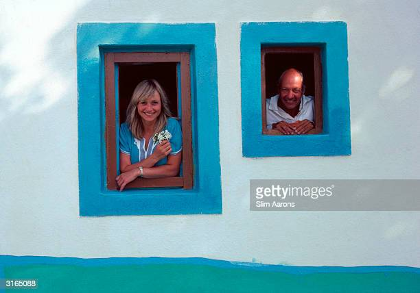 Actress Lizzie Spender and Iannis Goulandris look out of blue painted windows in a white wall in Patmos, Greece.