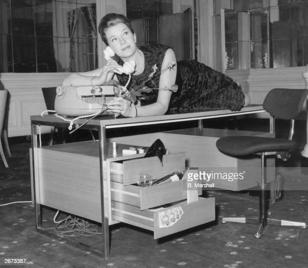 Actress Lois Maxwell who plays Miss Moneypenny in the Bond films drapes herself across a desk designed by Intra Design Ltd a company set up by the...