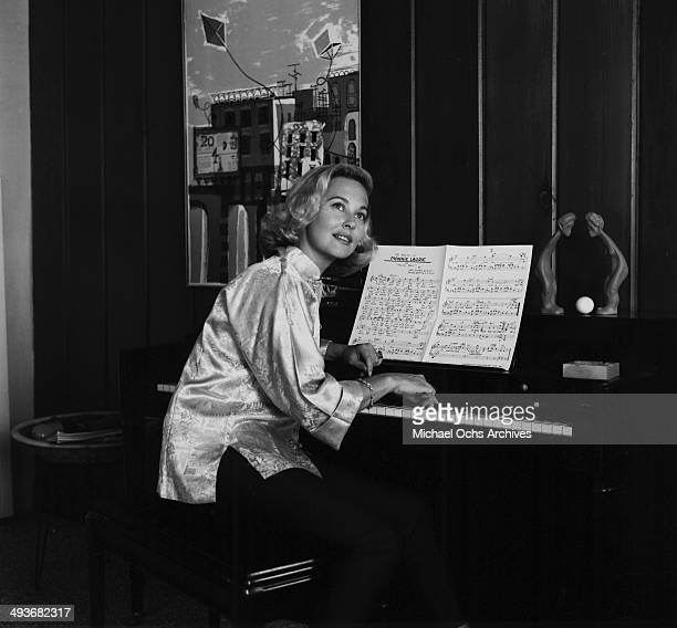 Actress Lola Albright poses at the piano in Los Angeles California