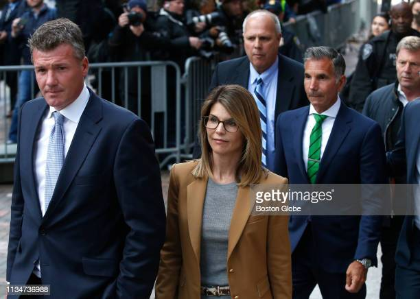 Actress Lori Loughlin in tan at center leaves as her husband Mossimo Giannulli in green tie at right follows behind her outside the John Joseph...
