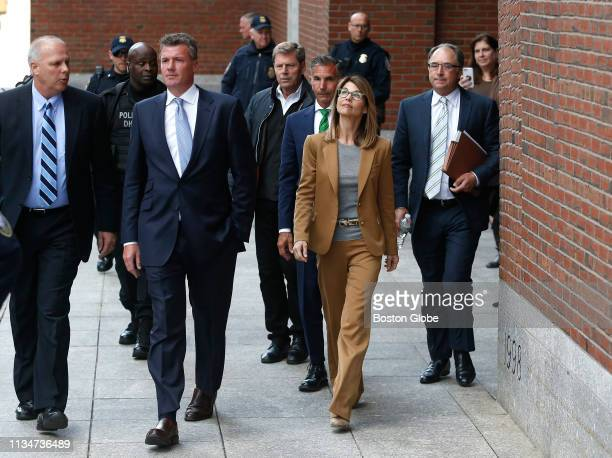 Actress Lori Loughlin in tan at right and her husband Mossimo Giannulli in green tie behind her leave the John Joseph Moakley United States...