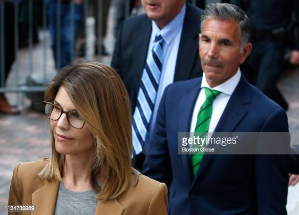 Actress Lori Loughlin left leaves as her husband Mossimo Giannulli right trails behind her outside of the John Joseph Moakley United States...