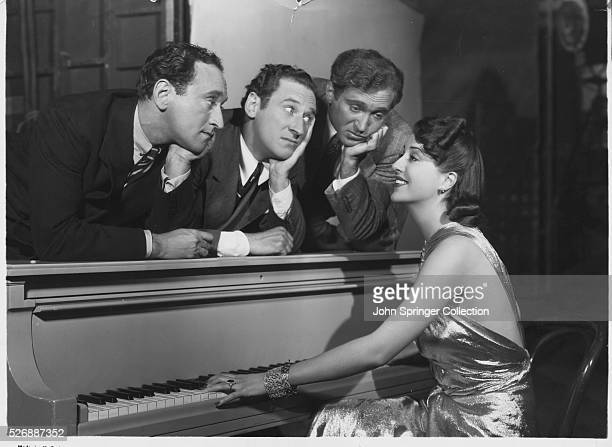 Actress Louise Hovick plays piano for Jimmy Al and Harry Ritz on the set of the 1937 film You Can't Have Everything