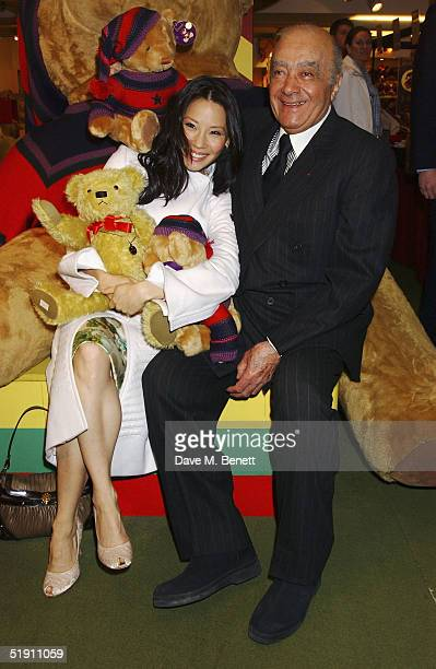 Actress Lucy Liu poses with owner Mohamed Al Fayed in front of a giant teddy bear this year's Harrods January Sale at the Knightsbridge store on...