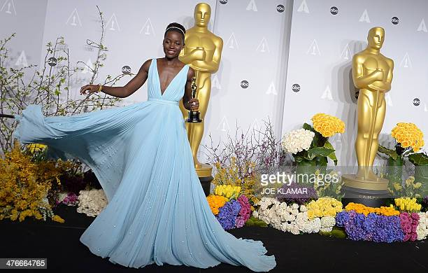 Actress Lupita Nyong'o celebrates winning Best Performance by an Actress in a Supporting Role award for '12 Years a Slave' in the press room during...