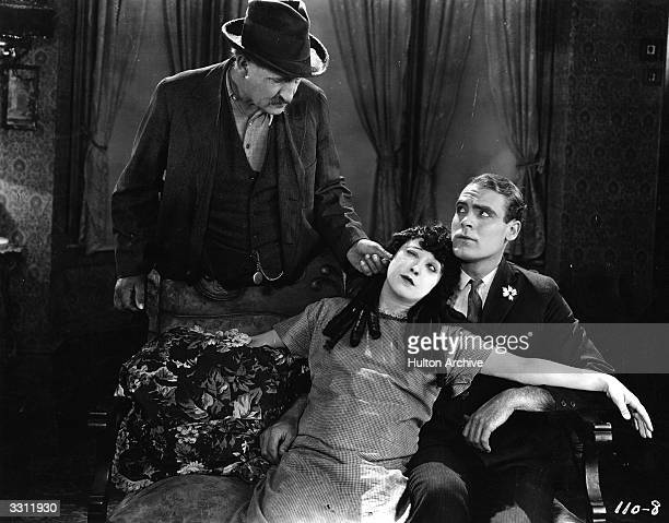 Actress Mabel Normand gets her ear pulled by a possessive father in this scene from the film 'The Extra Girl' Ralph Graves sits next to her on the...