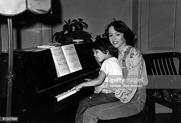 Actress Mackenzie Phillips poses for a portrait session at home holding a baby at the piano on December 3 1976 in Los Angeles California