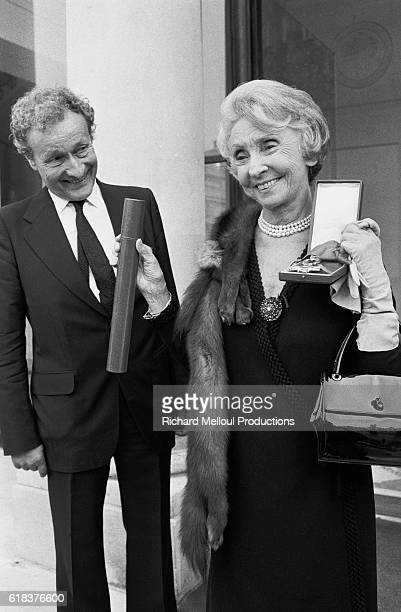 """Actress Madeleine Renaud holds the """"Legion d'Honneur"""" given to her by President Giscard D'Estaing at the Elysee Palace while her husband, actor..."""