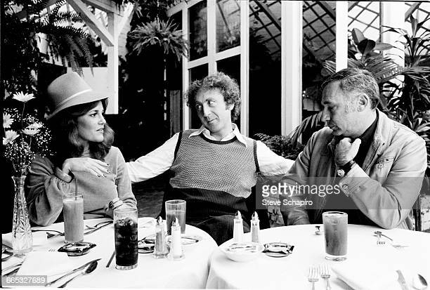 Actress Madeline Kahn actor Gene Wilder and actor/director Mel Brooks seated at an outdoor table Los Angeles California 1974