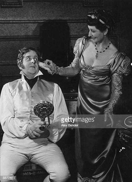 Actress Madge Compton tickles the face of Robert Morley with a rabbit's foot in a scene from 'The First Gentleman' at the Savoy Theatre in London