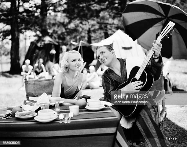 Actress Madge Evans watching actor Bing Crosby play the guitar during a break from filming 'Pennies from Heaven' for Columbia Pictures 1936