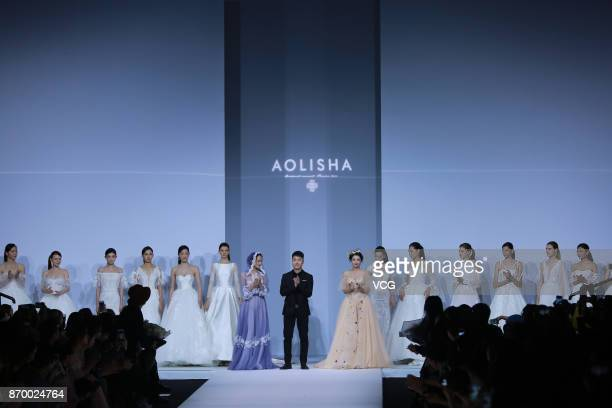Actress Madina Memet and actress Hai Lu showcase designs on the runway at Aolisha collection by designer Wei Xinkun during the MercedesBenz China...