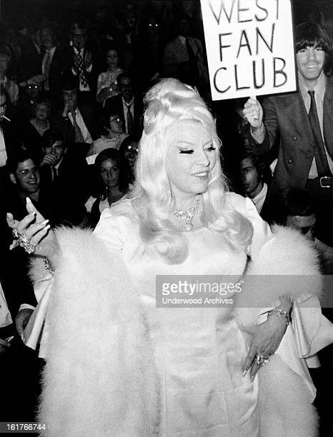 Actress Mae West greets the crowd of 10,000 fans who gathered to see her as she attended the premiere showing of the film, 'Myra Breckinridge' at the...