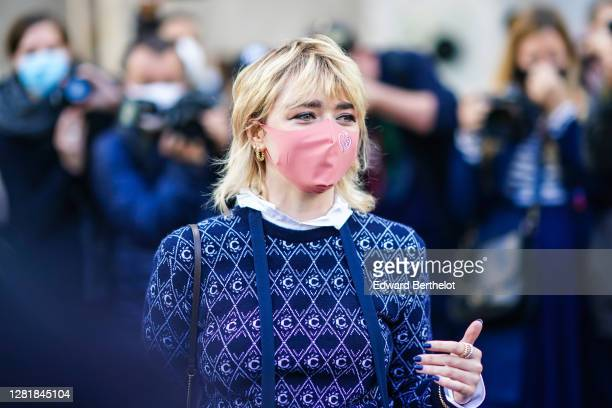 Actress Maisie Williams wears a pink protective face mask, a blue and purple wool pullover with printed geometric patterns, a white long shirt, beige...