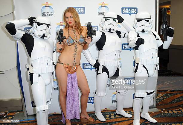 Actress Maitland Ward dressed as Slave Leia from Star Wars The Return of the Jedi poses with Stormtroopers at the 2014 Long Beach Comic Expo at the...
