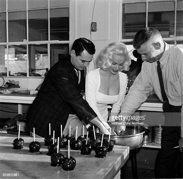 Actress Mamie Van Doren makes caramel apples with Ray Anthony during an event in Los Angeles,CA.