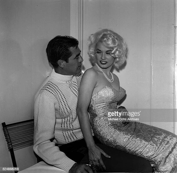 Actress Mamie Van Doren sits on the lap of actor Steve Cochrane during a party in Los AngelesCA