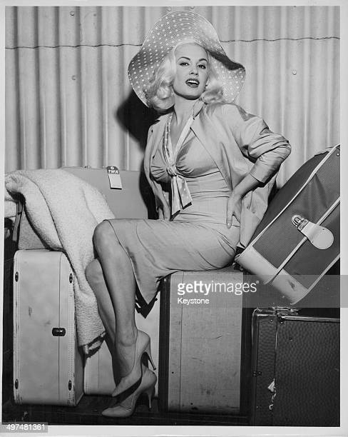 Actress Mamie Van Doren sitting in a glamorous pose on top of her luggage, as she arrives in New York with Trans World Airlines, Idlewild Airport,...