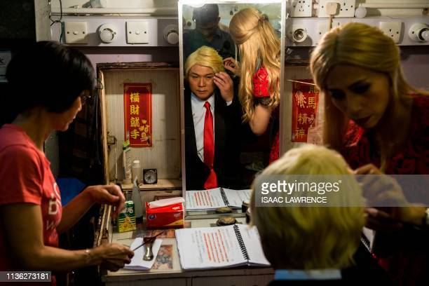 TOPSHOT Actress Man Chan dressed as Ivanka Trump helps actor Loong Koontin changes into US President Donald Trump back stage during a rehearsal of a...