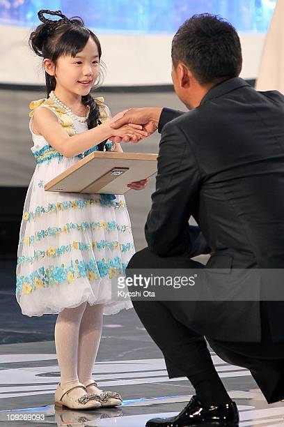 Actress Mana Ashida accepts the award for Rookie Of The Year for 'Ghost: Mou Ichido Dakishimetai' from presenter Ken Watanabe onstage during the 34th...