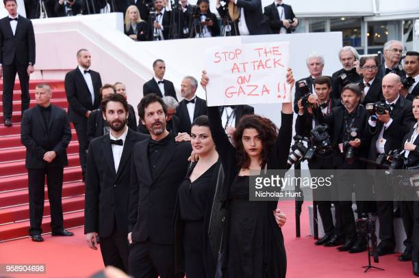 Actress Manal Issa holds a sign reading 'Stop the Attack on Gaza' as she poses with Director Gaya Jiji and director Etienne Kallos at the screening...
